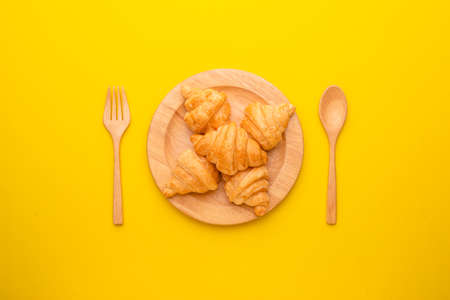 Top view mini Croissant in wooden dish on yellow background. Food concept with copy space Stockfoto
