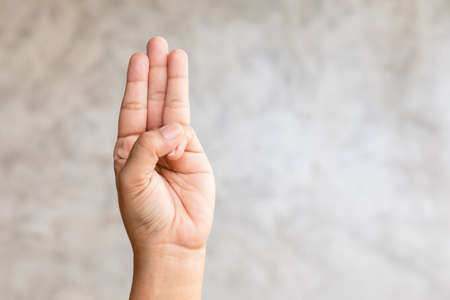 Close up hand showing three finger symbol on grey background with copy space Stockfoto