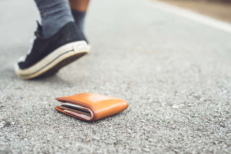 Asian man lose brown wallet on the road in tourist attraction. Losing wallet concept. Focus on wallet
