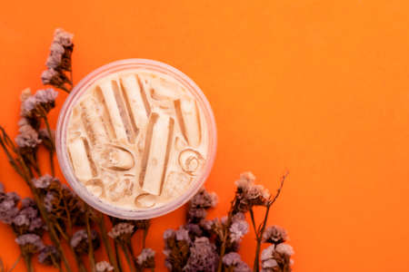 Top view bubble milk tea with ice in plastic glass on orange background