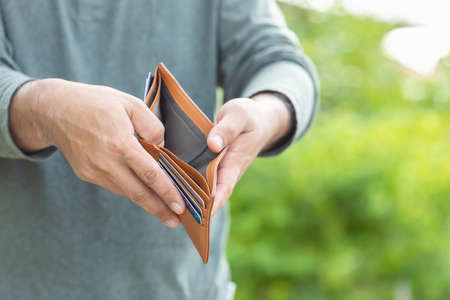 Asian man holding empty wallet. Money problem concept. Outdoor shooting with green blur background