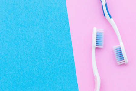 Top view new pink and blue toothbrush on pink background with copy space for text or design. Stockfoto