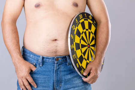 Fat people holding round yellow dartboard beside his belly position. Target of losing weight concept. Studio shot isolated on grey background Stockfoto