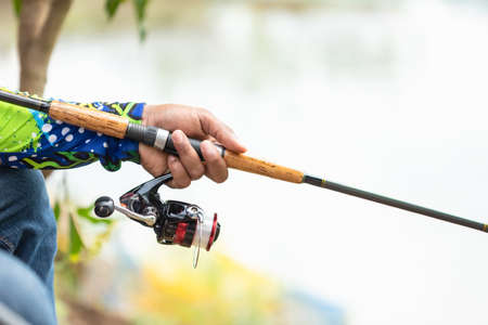 Close up fishing reel and rod in fisherman hand in a pond