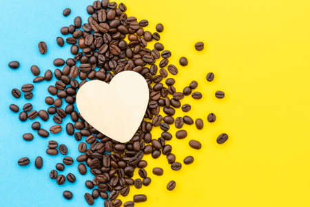 Love coffee concept, Top view white heart on the coffee grain on yellow background Stockfoto
