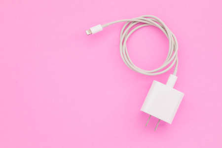 Top view new white smartphone charger on pink background with copy space for text or design Stockfoto