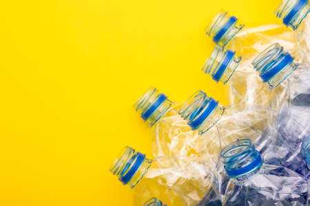 Top view old clear plastic water bottle on yellow background