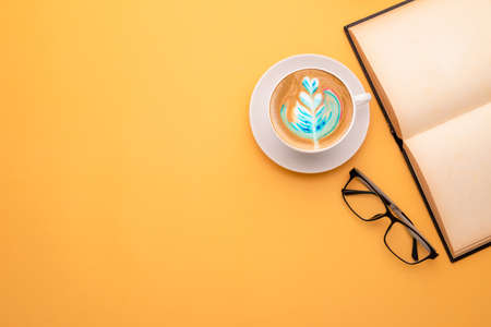 Top view white cup of hot Latte art coffee, book and eyeglasses on yellow background. Copy space for text or design