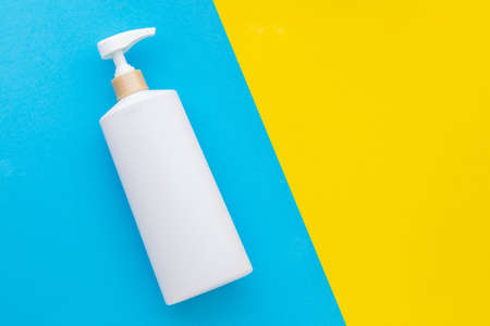 Top view blank white plastic pump bottle used for shampoo or soap on blue background