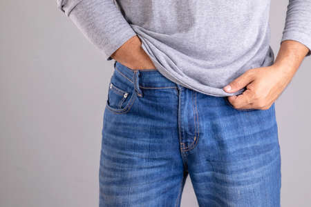 Itchy or Tinea Cruris concept. Man use hand scratching under his pant studio shot on grey background