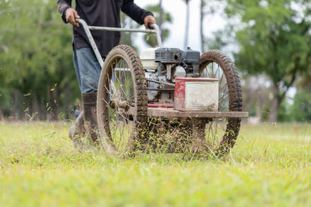 Thai worker mowing grass with machine in the public garden Imagens