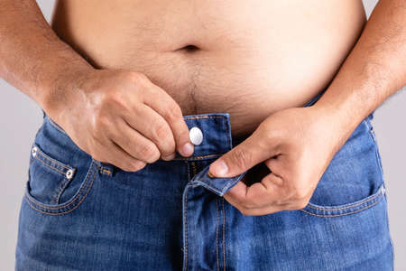 Close up fat man trying to button-up pants studio shot on grey background