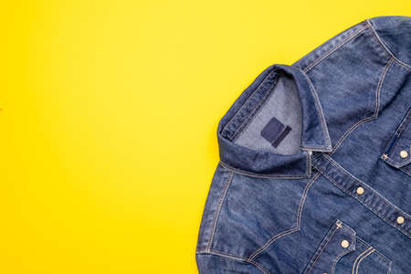 Recycle technology of plastic bottle to make clothes. Top view old water bottle and blue shirt jeans on yellow background