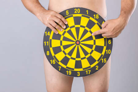 Man holding round yellow Dartboard to hide his penis position. Studio shot isolated on grey background Stockfoto