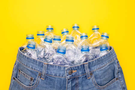 Recycle technology of plastic bottle to make clothes. Top view old water bottle and blue short jeans on yellow background Stockfoto