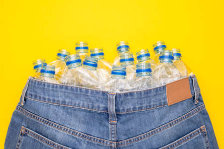 Recycle technology of plastic bottle to make clothes. Top view old water bottle and blue short jeans on yellow background