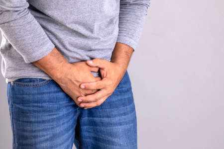 Pain on penis concept : Man use his hands to press on his penis on grey background