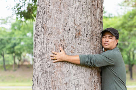 Tree hugging. Asian man giving a hug on big mango tree. Take care the earth, Love tree and nature or environment concept