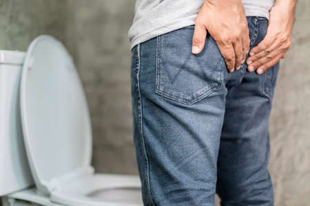 Close up man standing and holding on the back side in the toilet. Concept hemorrhoids