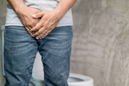 Men bladder problem concept : Man standing in the toilet and want to peeing and feeling pain in his penis. Health Care concept