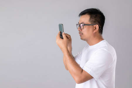 Short or long sighted concept : Man weraing eyeglasses and trying to look clearly on smarthphone in studio shot on grey background