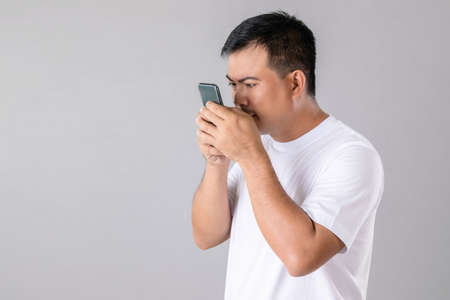 Short or long sighted concept : Man trying to look closer on smarthphone in studio shot on grey background