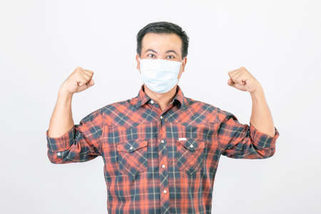Passed bad situation concept : Asian man wearing protective face mask in action of glad, victory or very happy isolated on grey background