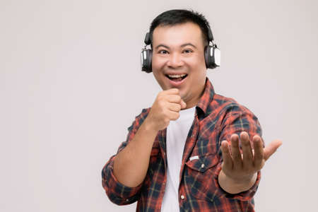 Portrait Asian man listening song or music from black headphone. Studio shot isolated on grey background Stockfoto
