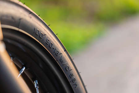 Macro number code on the front motorcycle rubber wheel. Outdoor shooting on the road with copy space