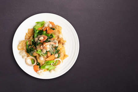 Top view. Fried noodle with seafood and vegetable in round white dish isolated on white background. Thai Food concept