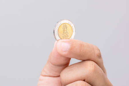 Close up hand holding Thailand coin (10 baht). Studio shot on grey background Stockfoto