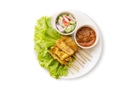 Top view. Pork Satay with Peanut Sauce and pickles which are cucumber slices and onions in vinegar. Isolated on white background
