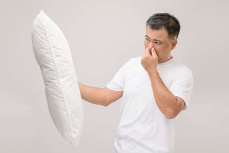 The pillow smells bad. Portrait Asian man holding white pillow and getting bad smell. Studio shot on grey background Stockfoto