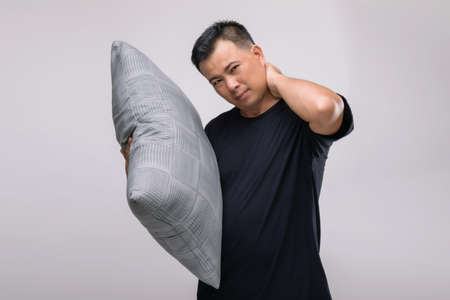 Neck aches concept : Portrait Asian man holding grey pillow and feeling tired or aches on his neck. Studio shot isolated on grey background