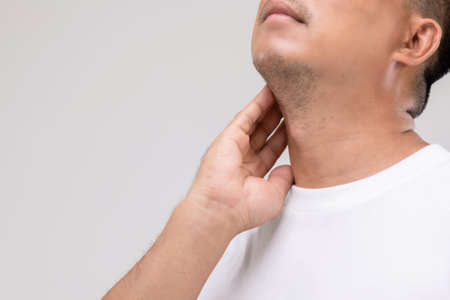 Lymphoma in men concept : Portrait Asian man is touching on his neck at lymph node position. Studio shot isolated on grey background