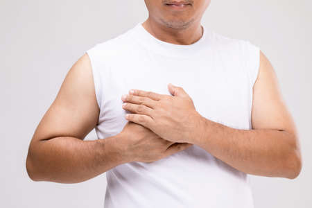Breast cancer in men concept : Portrait Asian man in posture of care or protect himself from  breast cancer. Studio shot isolated on grey background