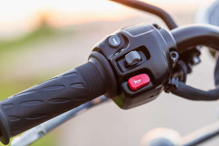 Red horn switch. Macro left handle bar with hand clutch of motorcycle. Motorcycle maintenance concept outdoor shooting with sunset effect