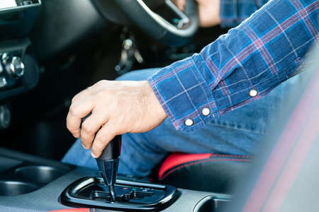 Car driving concept : Close up driver hand on automatic gear stick inside the modern car