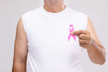 Breast cancer in men concept : Portrait Asian man and pink ribbon the symbol of breast cancer campaign. Studio shot isolated on grey background