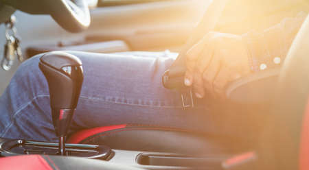 Car driving concept : Close up driver hand fastening on seat belt inside the modern car. Car interior with morning golden sun light flare effect. Transportation use