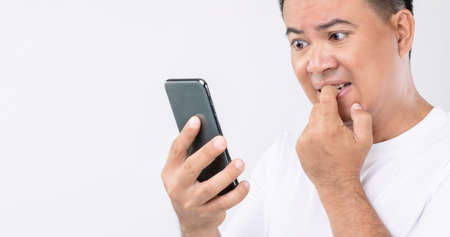 Nail Biting (Onychophagia) concept : Portrait people biting his nail while looking to smartphone. Studio shot isolated on grey background