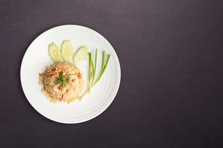 Top view. Fried rice with shrimp in round white dish isolated on black nature stone background. Thai Food concept