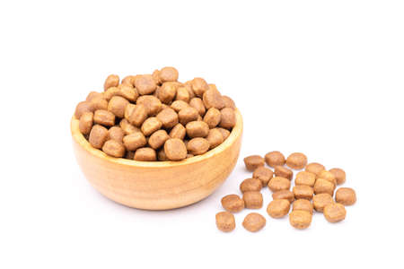 Pile of dog food in wooden bowl isolated on white background