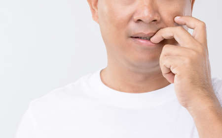 Nail Biting (Onychophagia) concept : Portrait people biting his nail. Studio shot isolated on grey background Stockfoto