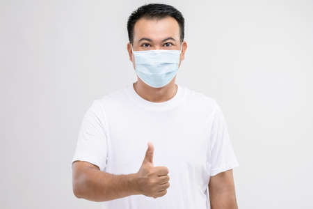 Portrait of Thai man wearing protective face mask to prevent virus studio shot on grey background
