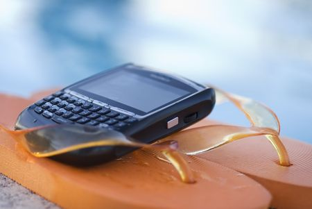 simplify: Flipflop thongs and Pda Cell Phone lying next to pool. Stock Photo