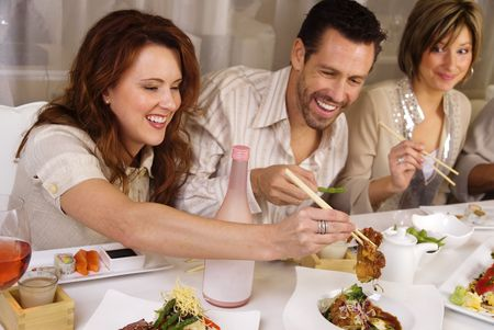Group of attractive people eating and socializing at a restaurant photo
