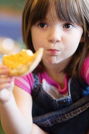 pretty little girl: Pretty little girl enjoying toasted bun,