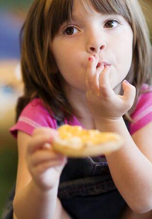 pretty little girl: Pretty little girl enjoying toasted bun, licking her lips