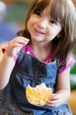 Pretty little girl enjoying toasted bun, smiling
